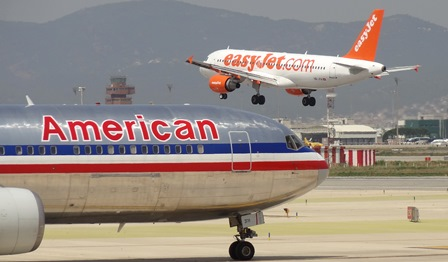 Un avión de American Airlines espera para despegar, mientras aterriza otro de Easyjet, en Barcelona-El Prat