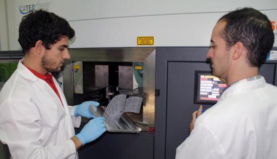 Dos técnicos de CATEC con una de las piezas fabricadas a través de la tecnología Additive Manufacturing en las instalaciones del centro