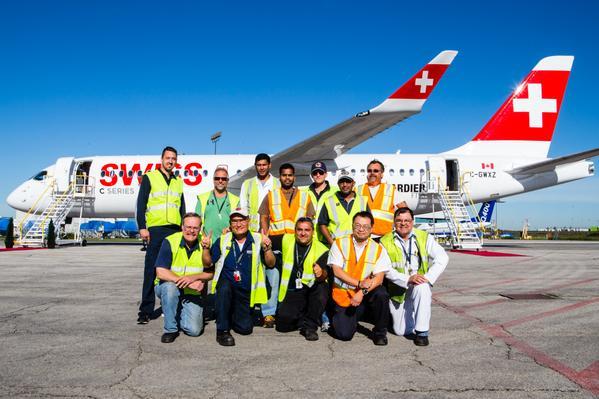 Empleados de Bombardier posan junto al primer CS100 de serie