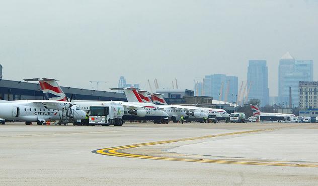 Aviones en la plataforma del aeropuerto. Al fondo, alguno de los rascacielos de la City