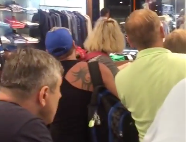 Un grupo de personas se protege en el interior de una tienda del aeropuerto